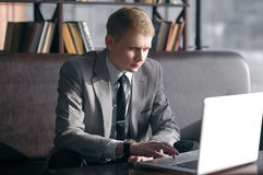 Businessman sitting at desk with laptop. Young businessman sitting at desk and working with laptop. looks at the laptop and moving fingers on the trackpad Stock Images