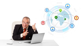Businessman sitting at desk and looking laptop with globe and so Stock Image