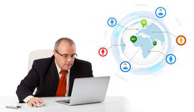 Businessman sitting at desk and looking laptop with globe and so Stock Photography