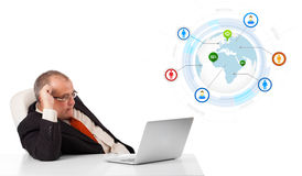 Businessman sitting at desk and looking laptop with globe and so Royalty Free Stock Photo