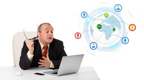 Businessman sitting at desk and looking laptop with globe and so Royalty Free Stock Image
