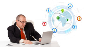Businessman sitting at desk and looking laptop with globe and so Stock Images