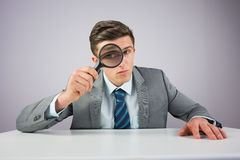 Businessman sitting at desk with magnifying glass Stock Photos