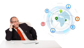 Businessman sitting at desk and making a phone call with globe a Stock Photos
