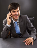 Businessman sitting at desk in office. Talking on  phone, smiling Royalty Free Stock Photo