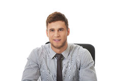 Businessman sitting by a desk in the office. Stock Photos
