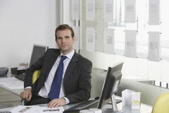Businessman Sitting At Desk In Office Stock Images
