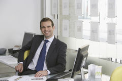 Businessman Sitting At Desk In Office Stock Image