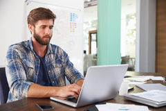 Businessman Sitting At Desk In Office Working On Laptop Stock Image