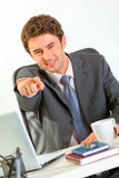 Businessman sitting at desk and pointing on you Royalty Free Stock Images
