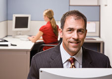 Businessman sitting at desk smiling Stock Photography