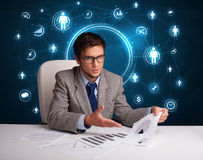 Businessman sitting at desk with social network icons Stock Photos