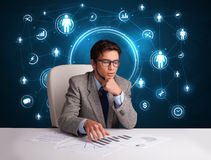 Businessman sitting at desk with social network icons Royalty Free Stock Photography