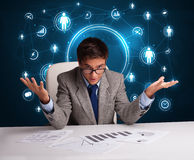 Businessman sitting at desk with social network icons Stock Photography