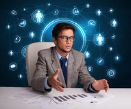 Businessman sitting at desk with social network icons Royalty Free Stock Photo