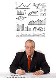 Businessman sitting at desk with statistics Stock Image