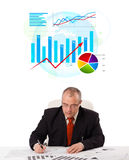 Businessman sitting at desk with statistics Stock Photos