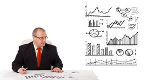 Businessman sitting at desk with statistics and graphs Stock Photography