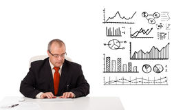 Businessman sitting at desk with statistics and graphs Stock Image
