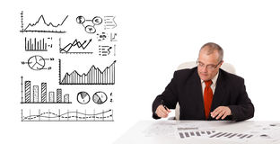Businessman sitting at desk with statistics and graphs Royalty Free Stock Photo