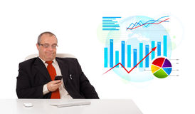 Businessman sitting at desk with statistics and holding a mobile Royalty Free Stock Photography