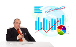 Businessman sitting at desk with statistics and holding a mobile Stock Photos