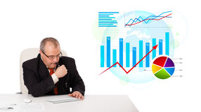 Businessman sitting at desk with statistics Royalty Free Stock Photography