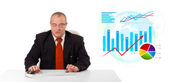 Businessman sitting at desk with statistics Royalty Free Stock Photos