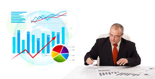 Businessman sitting at desk with statistics Stock Photography