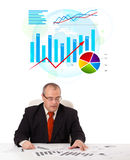 Businessman sitting at desk with statistics Royalty Free Stock Photo