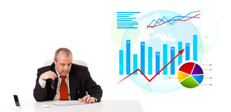 Businessman sitting at desk with statistics Royalty Free Stock Image