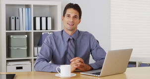 Businessman sitting at desk and talking to camera Stock Photos