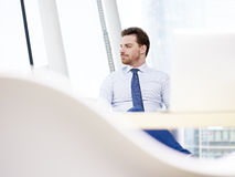 Businessman sitting at desk thinking Stock Photography