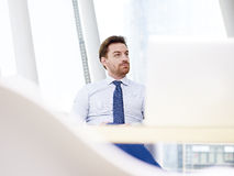 Businessman sitting at desk thinking Stock Image