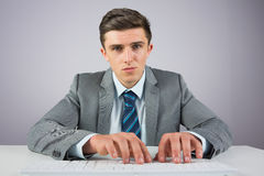 Businessman sitting at desk typing Royalty Free Stock Photo