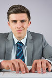 Businessman sitting at desk typing Royalty Free Stock Photography
