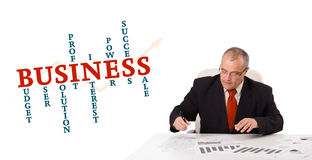 Businessman sitting at desk with word cloud. Isolated on white Stock Photography