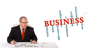 Businessman sitting at desk with word cloud. Isolated on white Royalty Free Stock Photography