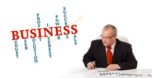 Businessman sitting at desk with word cloud. On white Royalty Free Stock Photo