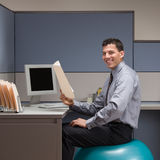 Businessman sitting on exercise ball at desk. Smiling businessman sitting on exercise ball at desk in cubicle Stock Photos