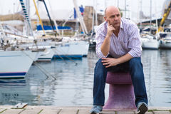 Businessman sitting by expensive sailing boats and yachts in a c. Oastal city, contemplating the views Stock Photo