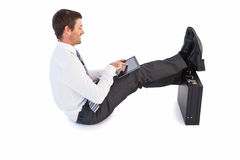 Businessman sitting with feet up while using his tablet Stock Photo