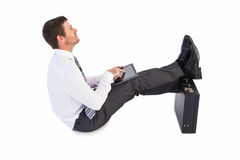 Businessman sitting with feet up while using his tablet Royalty Free Stock Images
