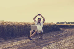 Businessman sitting in the field and working on laptop. Royalty Free Stock Image