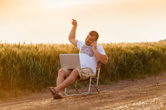 Businessman sitting in the field and working on laptop. Stock Image