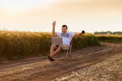 Businessman sitting in the field and working on laptop. Royalty Free Stock Photos