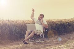 Businessman sitting in the field and working on laptop. Royalty Free Stock Photo