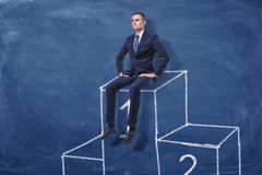 Businessman is sitting on the first place of a podium on blue blackboard background Stock Images