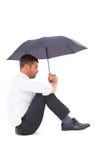Businessman sitting on the floor with black umbrella Stock Photo