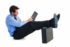 Businessman sitting on the floor with feet up on suitcase Royalty Free Stock Image